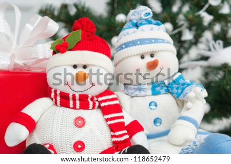 Two snowmen decoration by the Christmas tree with red gift box
