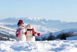 Two snowmen in the winter mountains