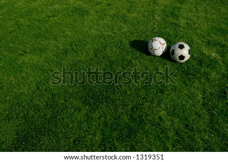Two soccer balls on green grass