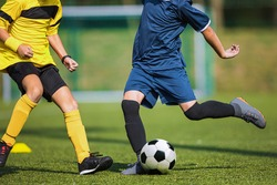 Two soccer players compete in a duel. Footballers kicking ball. Players in yellow and blue shirts. Soccer striker and defender playing tournament match