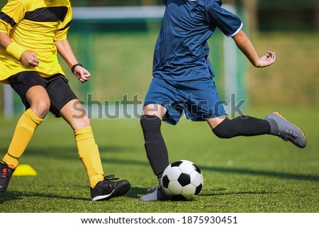 Photo of  Two soccer players compete in a duel. Footballers kicking ball. Players in yellow and blue shirts. Soccer striker and defender playing tournament match