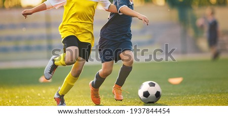 Two Soccer Players in a Duel on Grass Venue. Boys Running After Black and White Soccer Ball. Kids in Soccer Jersey Kits