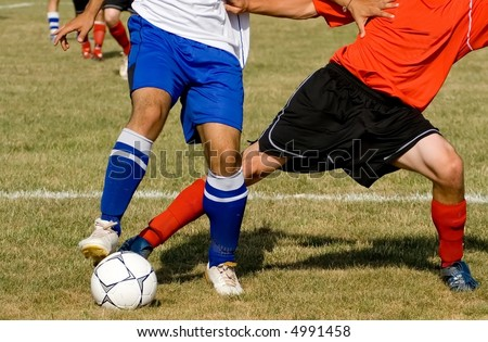 Two soccer players struggle for the ball.