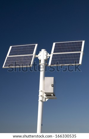 Two solar panels for green electricity mounted on a white post