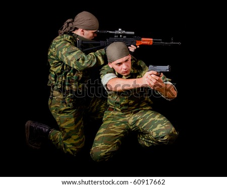 Two soldiers in camouflage uniform with weapon, isolated on black background