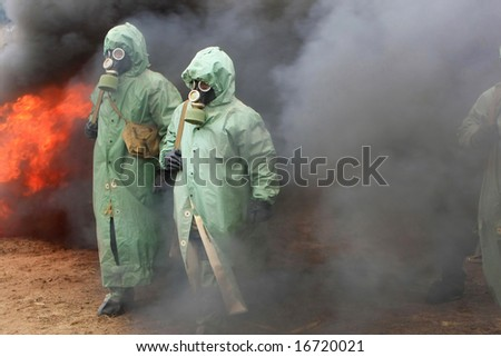 Two soldiers in chemical protection suites.