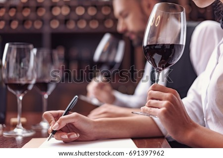 Two sommeliers, male and female tasting red wine and making notes at degustation card Stock photo ©