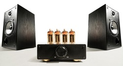 Two sound speakers with vacuum tube amplifier between them on white background.