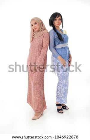 Two South east Asian Malay race ethnic origin woman wearing dress costume kebaya and baju kurung tuding headscarf on white background Photo stock ©
