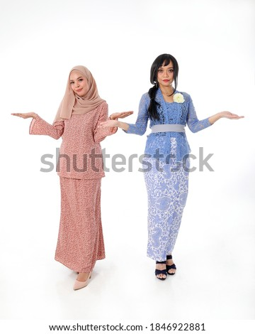 Two South east Asian Malay race ethnic origin woman wearing dress costume kebaya and baju kurung tuding headscarf on white background welcome hand gesture Photo stock ©