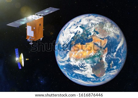 Two Space satellite orbiting the earth. Elements of this image furnished by NASA