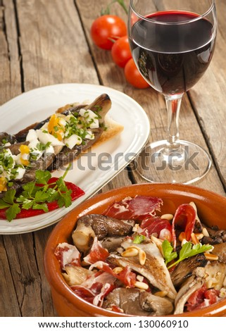 Two Spanish tapas with oyster mushrooms (setas),  with serrano ham and with eggs on toast.  With a grass of red rioja wine.