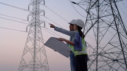 Two specialist electrical engineer working near to High voltage tower.