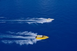 Two speed boats of white and yellow color fast motion on blue water top view. Aerial view luxury motor boat. Speed boats movement at high speed aerial view.