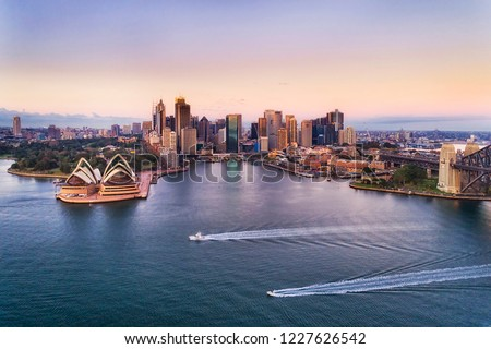 Two speed boats on calm waters of Sydney harbour in view of Circular quay and city CBD high-rise towers and Australian landmarks at sunrise with pink sky. #1227626542