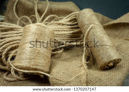 Two spools of burlap threads or jute twine and coil of linen rope on sackcloth fabric in close-up on grey background #1370207147