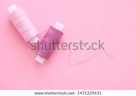 Two spools of sewing thread lilac (pink, violet, crimson) on a pink paper backgroun, copy space for text. Top view, flat lay. #1431229631