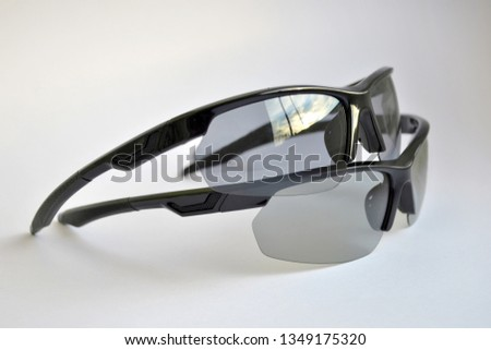 Two sport black sunglasses with photochromic and polarizing effect, one on the other, on white background #1349175320