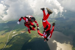 Two sports parachutist build a figure in free fall. Extreme sport concept.