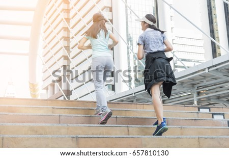 two sports woman running on stair with modern city, healthy lifestyle concept. #657810130