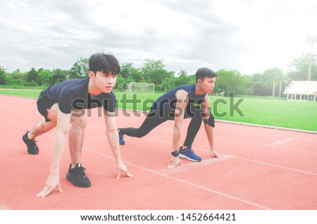 Two sportsman runners on starting position ready for competition in running at the stadium.