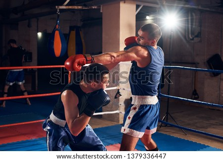 Two sportsmen aggressive boxers training boxing in the ring at the sport club