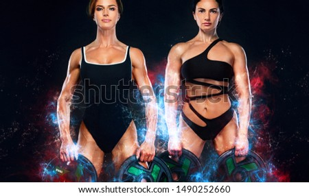 Two sporty and fit women athletes, bodybuilders with barbell. Workout and fitness motivation. Black background. Energy bodybuilding concept. Individual sports. Sports recreation.