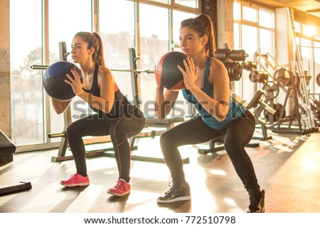 Two sporty girls doing exercises with fitness balls in the gym.