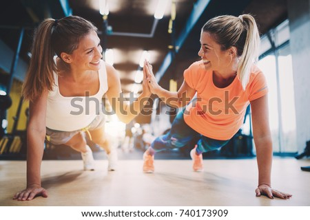 Two sporty girls doing push ups in gym