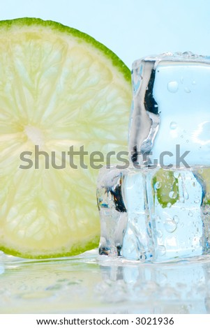 Two stacked ice cubes melted in water and slice of lime on reflection surface ready to be added to a cocktail