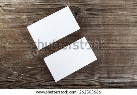 Two stacks of blank business cards on a dark wooden background. Template for branding identity. Top view.