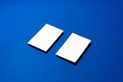 Two stacks of blank businesscards on blue background