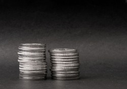 Two stacks of coins on a dark background