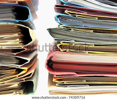 Two stacks of colorful folders over white background - stock photo