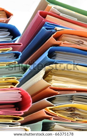 Two stacks of colorful office folders with documents