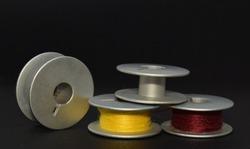 two stainless bobbin and two stainless bobbin with yellow and maroon thread on dark background.
