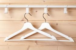 Two standard white hangers hang  near natural wooden wall, close-up photo
