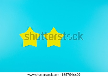 two star yellow paper note on blue background with copy space for text. Customer reviews, feedback, rating, ranking and service concept.