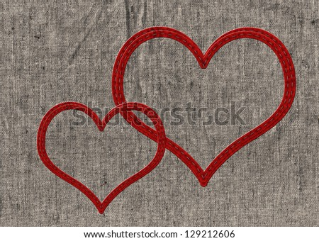 Two stitched red hearts on old linen - stock photo