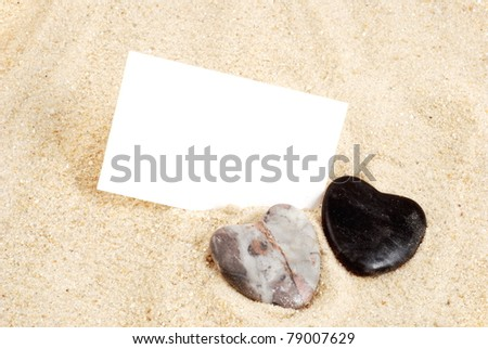 Two stone hearts in sand, with card
