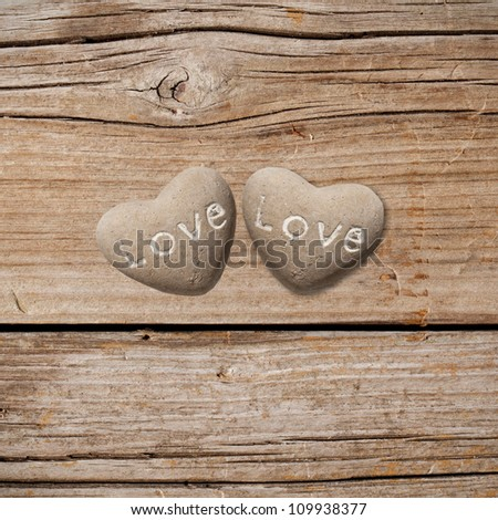 Two stone hearts on rustic wood