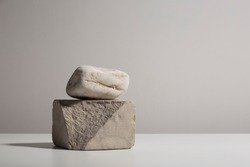 Two stones stacked on white table, minimalist home decor