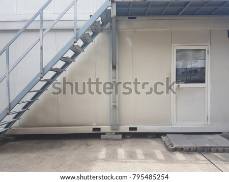 Two-storey container office with metal ladder and closed door.