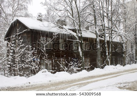 Two-storey wooden house with icicles in the snow. Russia #543009568