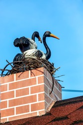 Two storks are sitting in a nest on a brick chimney stack on a red tiled roof against a blue sky.