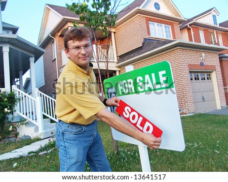 Two story house in a modern suburban neighbourhood with House For Sale Sign. The owner is attaching SOLD sign.