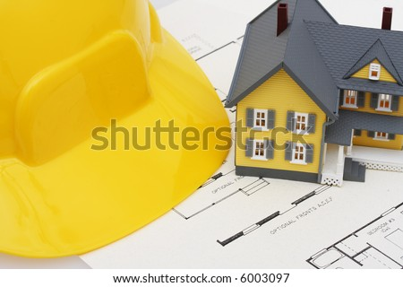 two story house with blueprints and hardhat