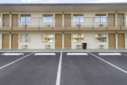 two story motel with parking lot in foreground