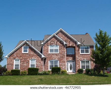 Two story new brick residential home with side garage and plenty of copy space.