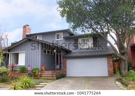 Two story ranch style house, gray wood siding with red brick work. Ranch style  is a domestic architectural style originating in the United States. #1041775264
